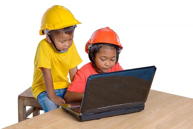 Asiatische kinder, die den schutzhelm tragen und hobel lokalisiert auf weißem hintergrund denken. kinder und bildungskonzept Premium Fotos