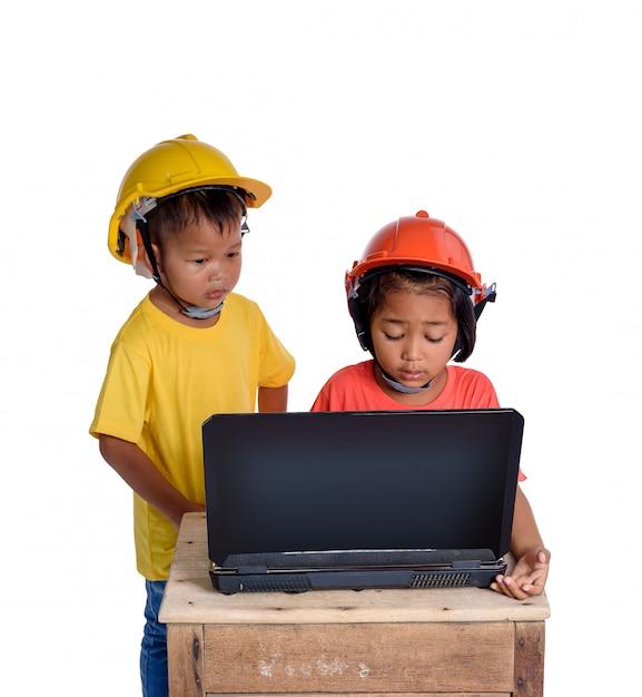 Asiatische kinder, die den schutzhelm tragen und hobel lokalisiert auf weißem hintergrund denken. Premium Fotos