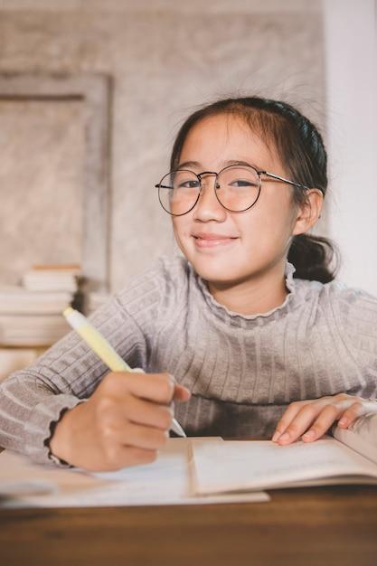 Asiatische kinder, die in der hand den gläsern mit dem stift studieren im hauptwohnzimmer tragen Premium Fotos