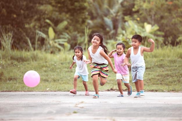 Asiatische kinder, die spaß haben, auf dem gebiet zusammen zu laufen und zu spielen Premium Fotos
