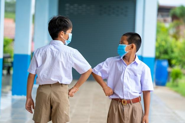 Asiatische kinder in schuluniform, die eine schutzmaske tragen, um sich gegen covid-19 zu schützen, schütteln sich gegenseitig die ellbogen, grüßen sich gegenseitig, begrüßen den ellbogen, verhindern coronaviren und distanzieren sich sozial. Premium Fotos