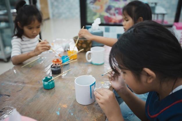 Asiatische kinder und freunde konzentrieren sich darauf, mit spaß zusammen mit öl auf keramikglas mit ölfarbe zu malen. kreative aktivitätsklasse für kinder in der schule. Premium Fotos