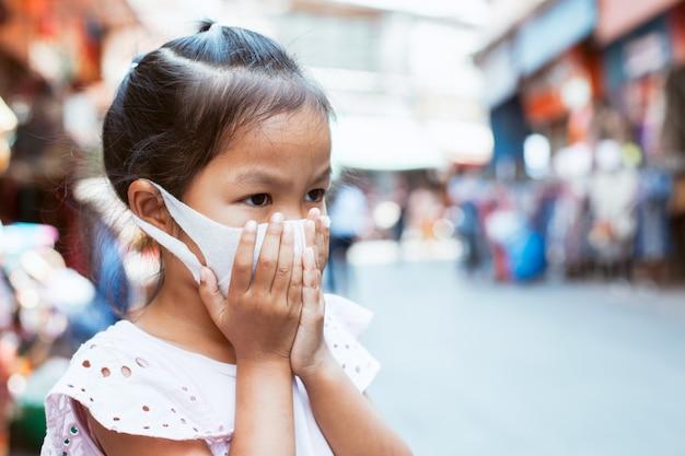 Asiatische kindermädchen mit schutzmaske gegen luftverschmutzung Premium Fotos