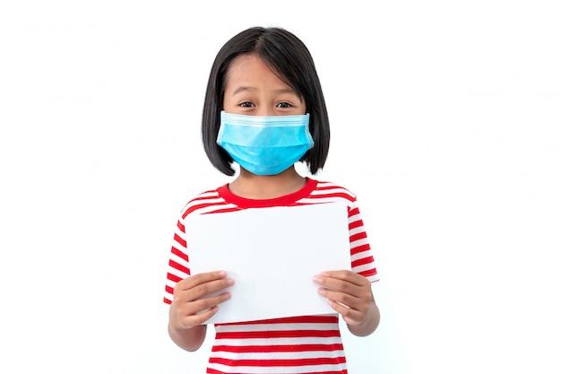 Asiatische kleine mädchen, die masken tragen, um die ausbreitung des coronavirus covid-19 mit einem leeren weißen papier auf weiß zu verhindern Premium Fotos