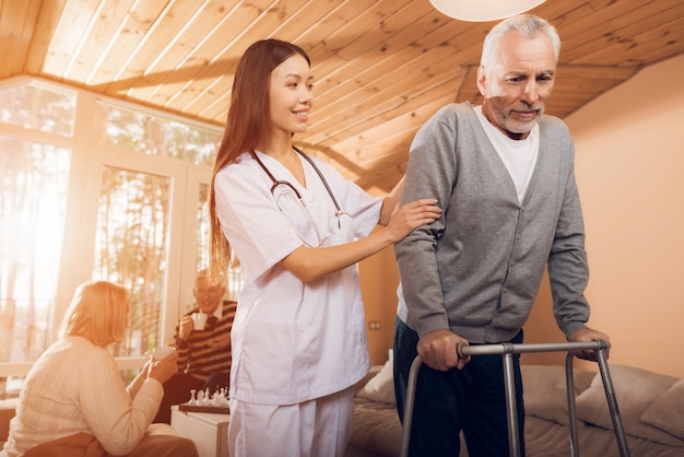 Asiatische krankenschwester hilft mann auf einem erwachsenen wanderer in einem pflegeheim Premium Fotos