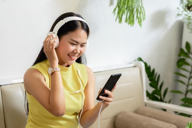 Asiatische lächelnde studentin tragen drahtlose kopfhörerstudie online mit skype-lehrer in einem café, Premium Fotos