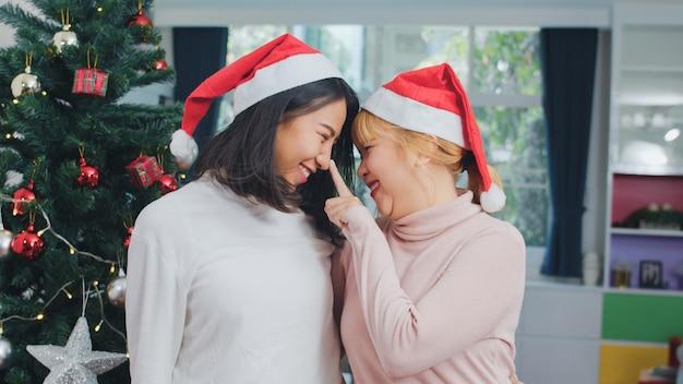 Asiatische lesbische paare feiern weihnachtsfest. lgbtq weiblicher jugendlich abnutzungs-weihnachtshut entspannen sich glückliches lächelndes schauen genießen weihnachtswinterurlaube zusammen im wohnzimmer zu hause. Kostenlose Fotos