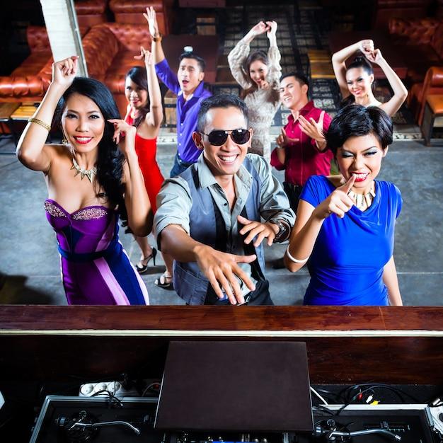 Asiatische leute, die auf tanzfläche im nachtklub feiern Premium Fotos