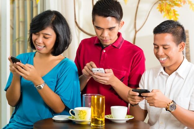 Asiatische leute, die spaß mit handy haben Premium Fotos
