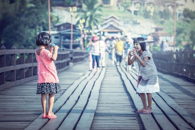 Asiatische mädchen, die an einem dosentelefon sprechen Premium Fotos