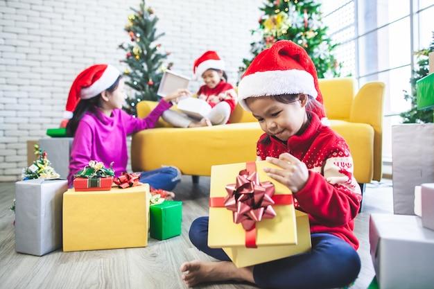 Asiatische mädchen überraschen mit geschenken und helfen, gemeinsam zu dekorieren, um im weihnachtsfest zu feiern Premium Fotos