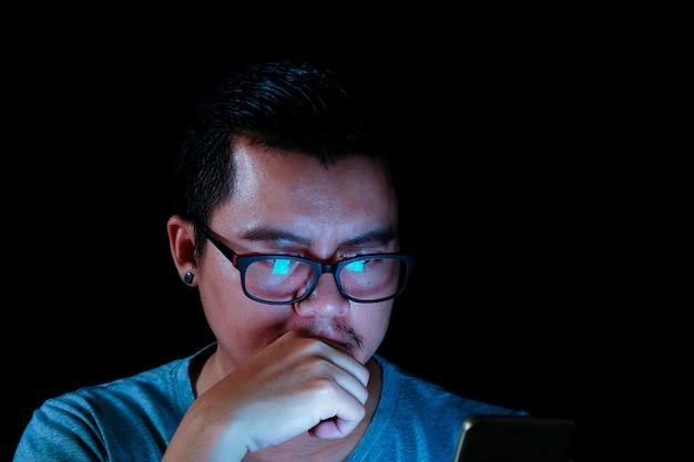 Asiatische männer benutzen das telefon oder die tablette mit einem blaulicht in der dunkelheit, konzepteffekte der technologie. Premium Fotos