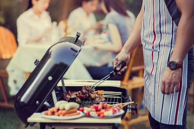 Asiatische männer kochen für eine gruppe freunde, um grill zu essen Premium Fotos