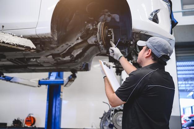 Asiatische männliche autotechnikerautowartung für kunden entsprechend spezifiziertem fahrzeug Premium Fotos