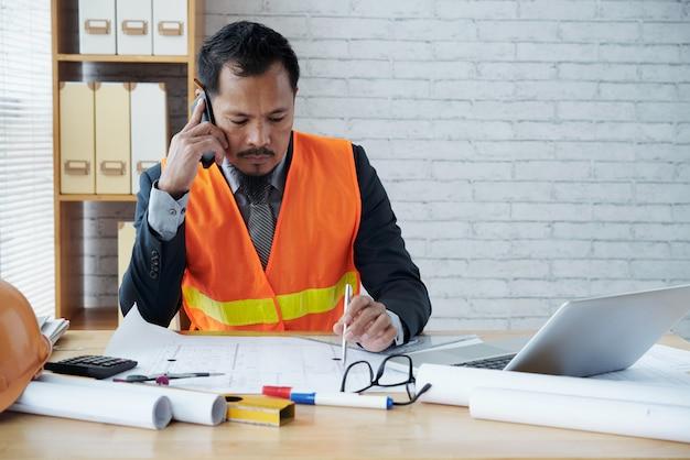 Asiatische männliche baufirmaexekutive, die im büro sitzt und am telefon spricht Kostenlose Fotos