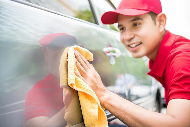 Asiatische mannarbeitskraft in einer roten uniform, die glücklich ein auto mit einem gelben microfiber stoff säubert Premium Fotos