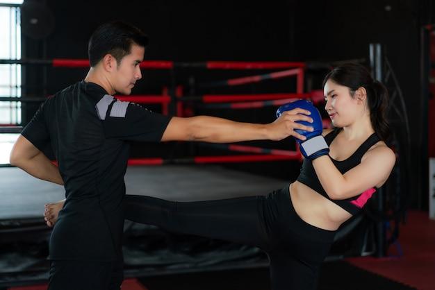 Asiatische mannberufstrainerpraxis, die zum boxer der jungen frau im boxstadion tritt Premium Fotos