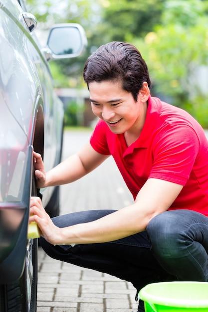 Asiatische mannreinigungsautofelgen mit schwamm Premium Fotos