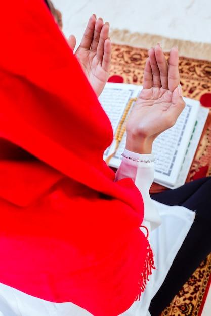 Asiatische moslemische frau, die mit dem koran betet Premium Fotos