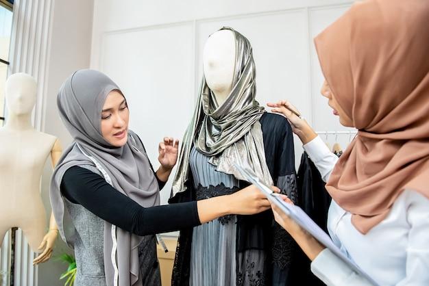 Asiatische moslemische frauenmodedesigner, die schneiderei bearbeiten Premium Fotos