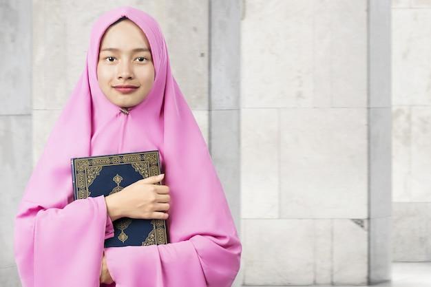 Asiatische muslimische frau in einem schleier, der den koran steht und hält Premium Fotos