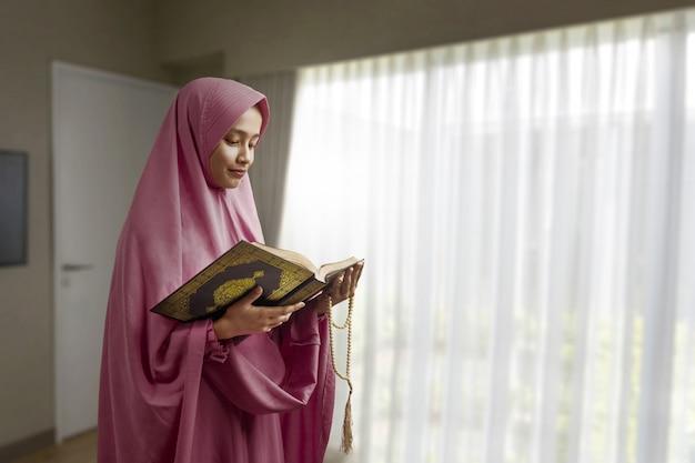 Asiatische muslimische frau in einem schleier, der gebetsperlen hält und den koran liest Premium Fotos