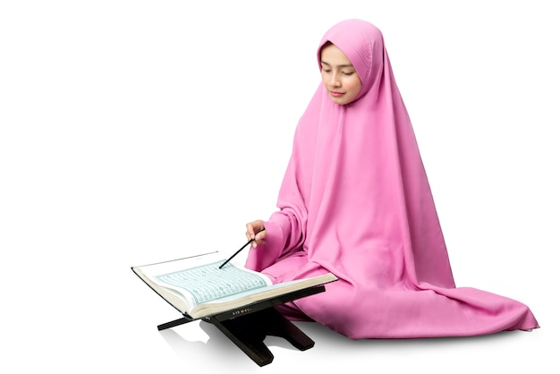 Asiatische muslimische mannfrau in einem schleier, der den koran sitzt und liest Premium Fotos