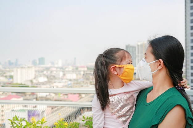 Asiatische mutter, die ihre tochter mit dem tragen einer schutzmaske gegen luftverschmutzung pm 2,5 in bangkok-stadt trägt. thailand. Premium Fotos