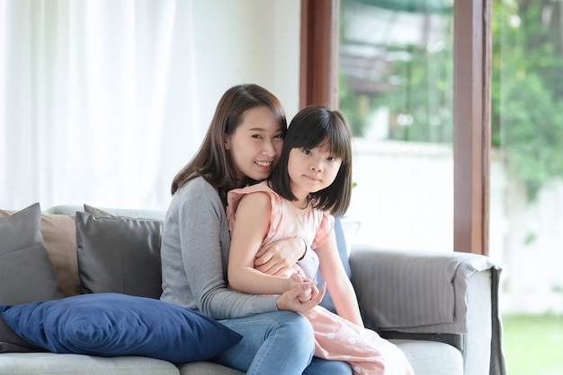 Asiatische Mutter, Die Ihre Tochter Mit Dem Tragen Einer