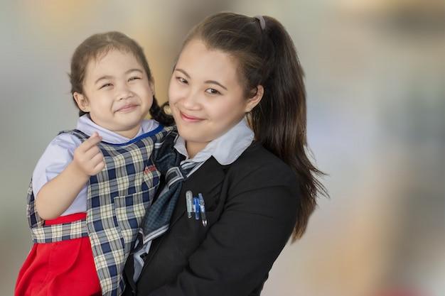 Asiatische mutter und kind, die mit liebe auf unscharfem hintergrund für frohes glückbild der lebensstilfamilie lächelt und umarmt. Premium Fotos