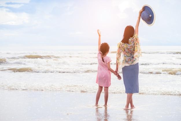 Asiatische mutter und tochter halten die hände am strand Premium Fotos