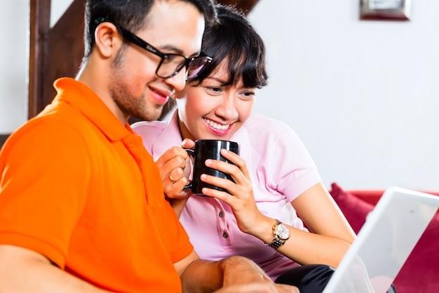 Asiatische paare auf der couch mit einem laptop Premium Fotos