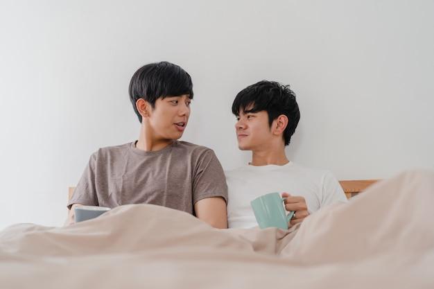 Asiatische paare der homosexuellen männer, die die schöne zeit am modernen haus haben sprechen. das junge glückliche asien-liebhabermann entspannen sich restgetränkkaffee nach wachen beim morgens liegen auf bett im schlafzimmer am haus auf. Kostenlose Fotos