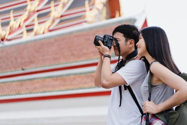 Asiatische paare des reisenden, die kamera für verwenden, machen ein foto, während urlaubsreise in bangkok, thailand verbringen Kostenlose Fotos