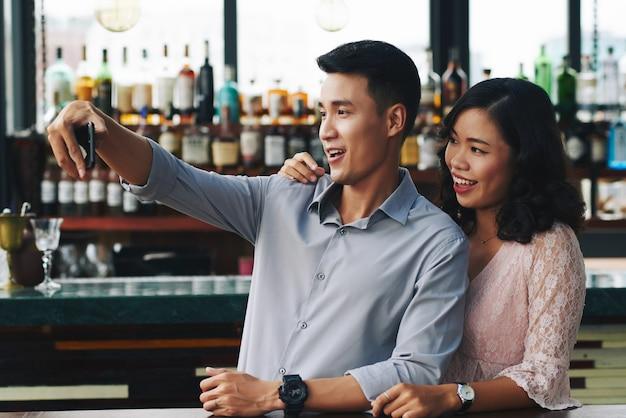 Asiatische paare, die selfie auf smartphone in der stange nehmen Kostenlose Fotos