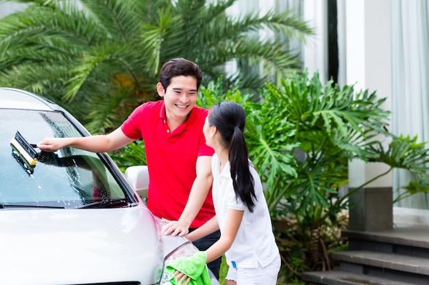 Asiatische paare, die zusammen auto säubern Premium Fotos