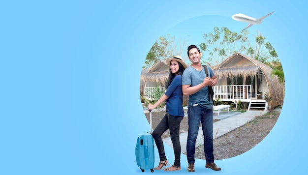 Asiatische paare mit der koffertasche und rucksack, die mit häuschenhintergrund stehen Premium Fotos