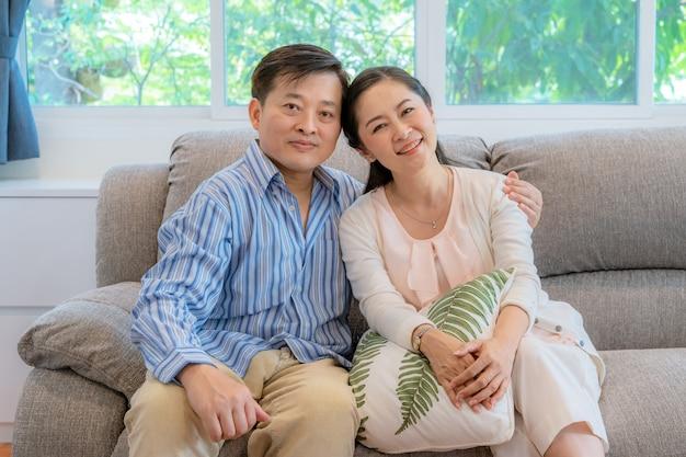 Asiatische paare mittleren alters sitzen und entspannen auf dem sofa im wohnzimmer. Premium Fotos