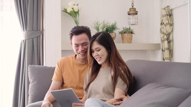 Asiatische paare unter verwendung der tablette für das on-line-einkaufen im internet im wohnzimmer zu hause, süßes paar genießen Kostenlose Fotos