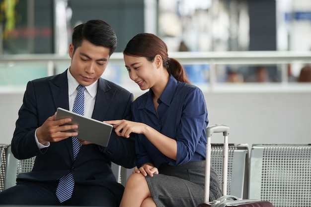 Asiatische paare unter verwendung des tablets im flughafen Kostenlose Fotos