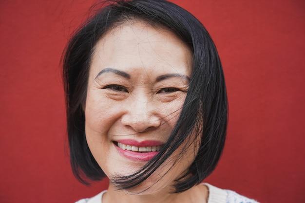 Asiatische reife frau, die vor kamera lächelt - porträt der älteren frau mit rotem hintergrund - freudiger älterer lebensstil und reales personenkonzept - fokus auf gesicht Premium Fotos