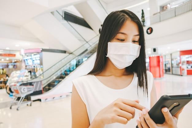 Asiatische reisende frau mit maske und handy im einkaufszentrum für neues normales lebensstilkonzept Premium Fotos