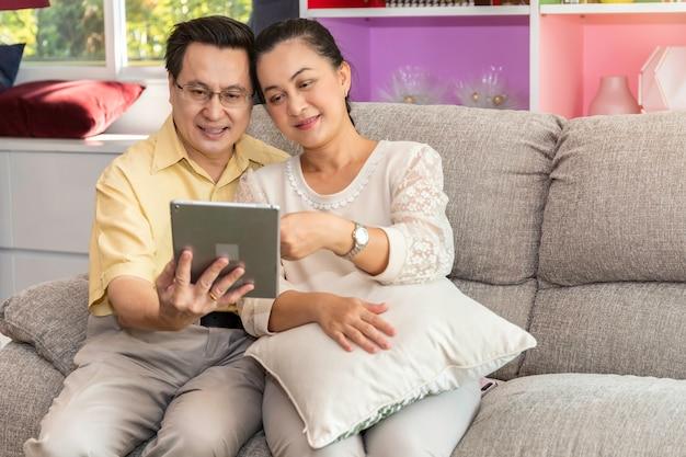 Asiatische schauende tablette der älteren paare im ruhestand im pflegeheim. Premium Fotos
