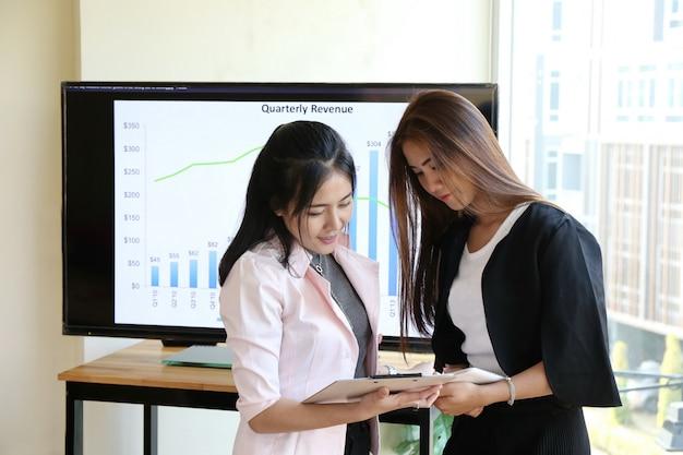 Asiatische schicke intelligente frauenhandarbeit der reizend schönen sonnenbräunehaut am laptoptelefon und schreiben stift auf notizbuchmolkerei auf holztisch im büro. präsentieren sie ihr produkt mit frau gute arbeitsleistung. Premium Fotos