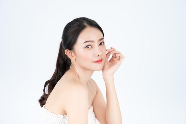 Asiatische schöne frau im weißen unterhemd zeigt helle und gesunde haut. Premium Fotos