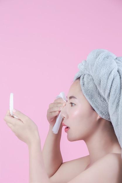 Asiatische schöne frau säubert das gesicht auf einem rosafarbenen hintergrund. Kostenlose Fotos