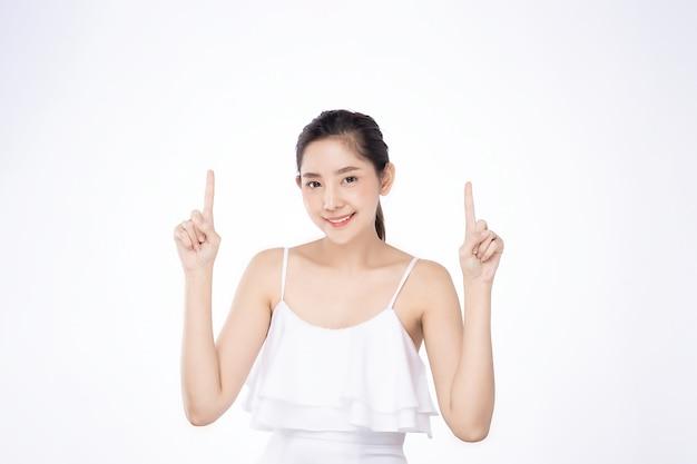 Asiatische schöne junge frau, die beide hand mit dem finger auf oberseite mit lächelngesicht zeigt Premium Fotos