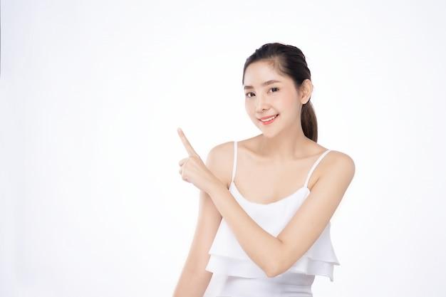 Asiatische schöne junge frau, die eine hand mit dem finger auf oberseite mit lächelngesicht zeigt Premium Fotos