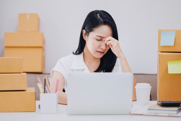 Asiatische schöne junge geschäftsfrau, die kopfschmerzen und druck in den büroräumen mit produktkasten glaubt. Premium Fotos