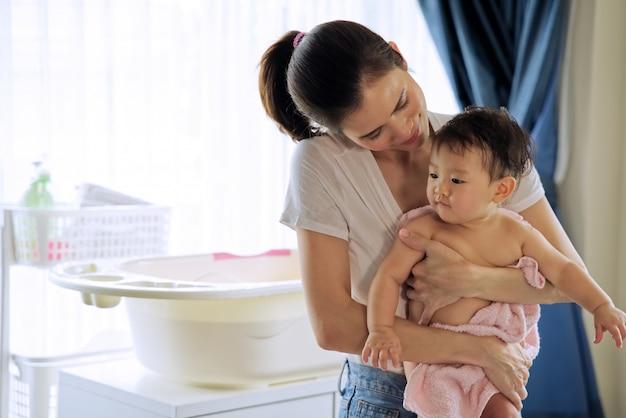 Asiatische schöne mutter, die kleines nettes baby hält, nachdem ein bad genommen worden ist und und ihr kind stehen im raum geschaut worden sind Premium Fotos